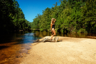 Woman in swimsuit tanding on gnarled log on sand bar