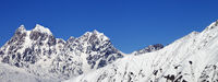 Panoramic view on snowy mountains and blue clear