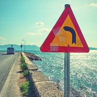 Road sign on corner of road by the sea
