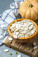 Unpeeled pumpkin seeds in a wooden bowl.