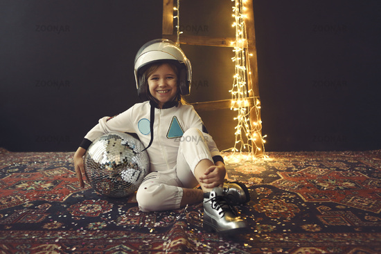 Astronaut futuristic kid girl with white full length uniform and helmet wearing silver shoes