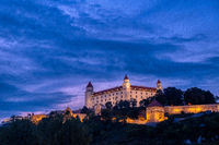 Bratislava castle illuminated in evening glow against dramatic sky