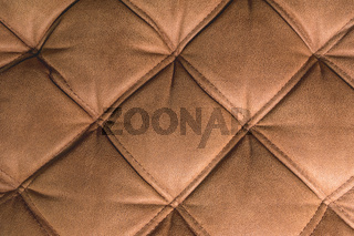 A close-up of a fragment of an expensive brown textile sofa in the room