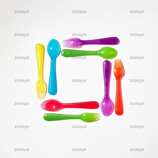 Square from colorful plastic cutlery on a light background.