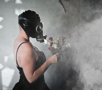 Woman in gas mask holding flowers