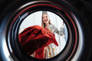 Young woman at home puts the dress in the drying machine.