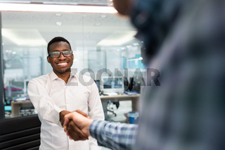 Reaching hands of black and caucasian race. Businessmans finishing their meetings with handshake of a successed job.