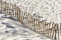 Zaun aus Draht und Holz auf sandigem Gelände