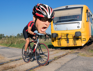 Terrified cyclist is rushing before by train on the tracks. Shocked biker ride a railway crossing in front of an approaching train. The regional train coming to a road with a hurry bicyclist on a crossing.