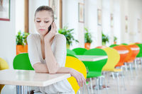 beautiful woman sits in the cafe and talking on mobile phone
