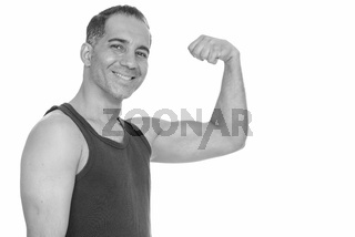 Mature happy Persian man flexing arm getting ready for gym flexing arm