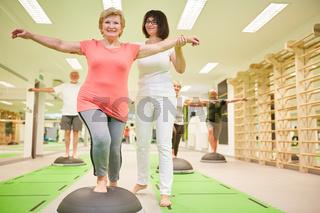 Trainerin gibt Seniorin Hilfestellung beim Balance Training