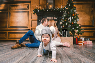 family holiday New Year and Christmas. Young caucasian family mom dad son 1 year sit wooden floor near fireplace christmas tree on Christmas evening. Baby learning walk creeps background parents
