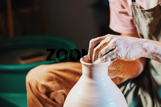 Overhead view of man making jug on pottery wheel. Potter shapes the clay product - jug - with professional tools, top view. Small business owner working in workshop.
