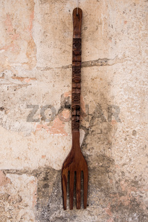 Giant wooden fork hanged on a stone brick wall.