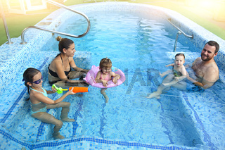 Happy family with little kids having fun together in the pool