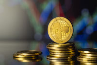 Ripple coin and virtual money concept. Gold Ripple on a stack of coins with chart of growing and falling valuance of a cryptocurrency. Mining or blockchain technology.