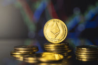 Ethereum and virtual money concept. Gold ethereum on a stack of coins with chart of growing and falling valuance of a cryptocurrency. Mining or blockchain technology.