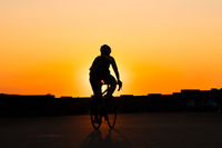 silhouette of a person riding bicycle with sunset sky background