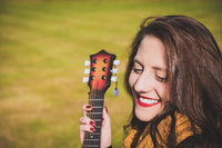 Vivacious happy young woman with a guitar