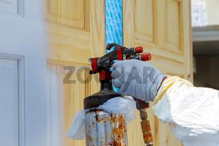 Hand with spray gun painting wooden door