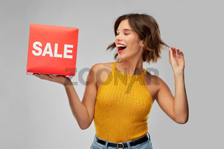 happy smiling young woman posing with sale sign