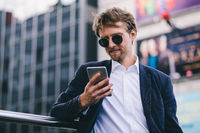 A Young Guy With Blonde Hair In Sunglasses Looks At His Mobile Phone While Being Outdoors On A Summer Day