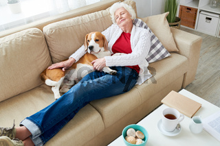 Tired pet owner relaxing with dog on sofa