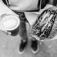 Female Hands Holding Delicious Organic Salmon Vegetarian Burger and Homebrewed IPA Beer.