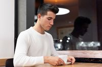 Young man at coffee shop in early morning with a white coffee mug at table.
