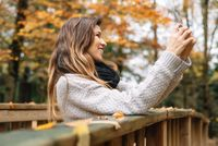 Beautiful young happy woman taking selfie with smartphone in autumn park. Season, technology and people concept.