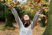 Happy Woman Throwing Leaves in autumn park.