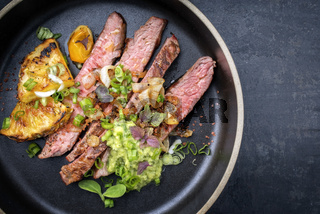 Modern Barbecue dry aged wagyu flank steak with pineapples and chimichurri sauce as top view on a plate with copy space right