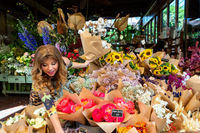 Woman on footpath choosing bunches of flowers from florist