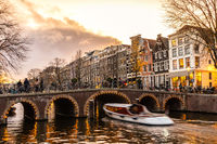 Beautiful tranquil scene of city of Amsterdam at dusk. Bicycles along the street and on the bridge over the canal.