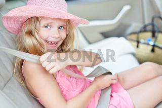 Kind im Auto beim Anschnallen von Sicherheitsgurt
