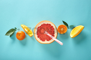 Orange slices and a half of grapefruit with a straw on a blue background in the form of a pattern