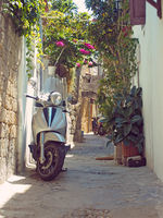 a scooter parked in a narrow typical quiet cobbled street in rhodes town with old yellow painted houses and a stone arch with sunlit summer sky