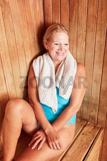 Lächelnde Seniorin entspannt in der Sauna