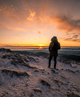 Hiker standing on a rocky mountain summit watching the golden glow of the rising sun at dawn over a winter landscape