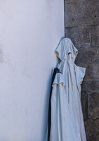 Ghostly shape formed by folded street umbrella