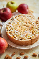 Freshly baked homemade apple pie with almond flakes cake on yellow