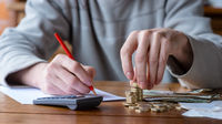 Close up man with calculator counting, making notes at home, hand is writes in a notebook. Stacked coins arranged at deesk. Savings finances concept.