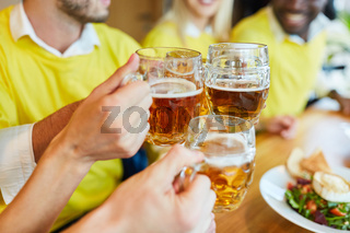 Hände halten Bierglas beim Anstoßen in einer Bar
