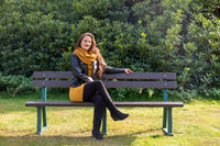 Attractive stylish woman seated on a park bench