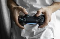 Gamer in white tshirt holding a gamepad in hands. Man hands playing a video game with a black controller. Play a video game at home with a pleasure.