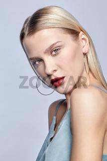 Blonde female on gray background.
