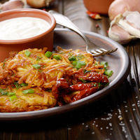 Homemade tasty potato pancakes in clay dish with sun-dried tomatoes and sour cream
