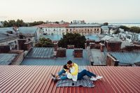 Loving young couple is sitting on the roof of the house.