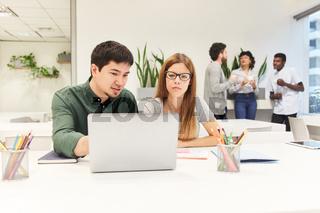 Business Kollegen arbeiten zusammen am Laptop